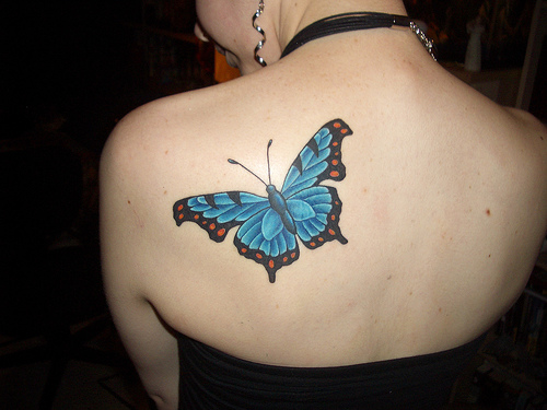 A woman with a blue butterfly tattooed on the back of her left shoulder.